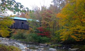 Vermont foliage in its glory with bright reds, yellows and oranges by a covered bridge